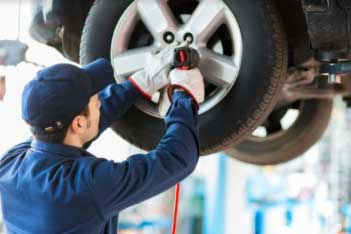 mechanic fixing tire on garage shop