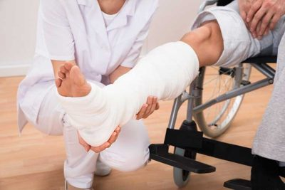 Nurse holding injured right leg with plaster cast, workers compensation