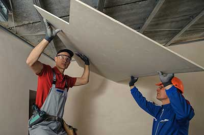 Two workers installing ceiling, NY Contractors Insurance